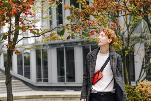 Thoughtful man looking while standing against building during autumn - OGF00905