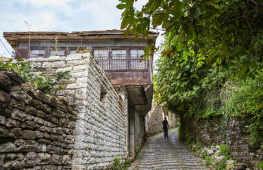Man walking on footpath by house at Gjirokaster, Albania - MAMF01635