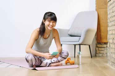 Smiling woman using smart phone while sitting cross-legged at home - AODF00316