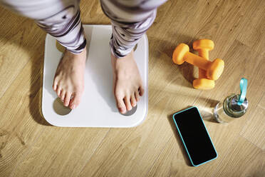 Woman checking weight while standing on weight scale by dumbbell, water bottle and mobile phone at home - AODF00325