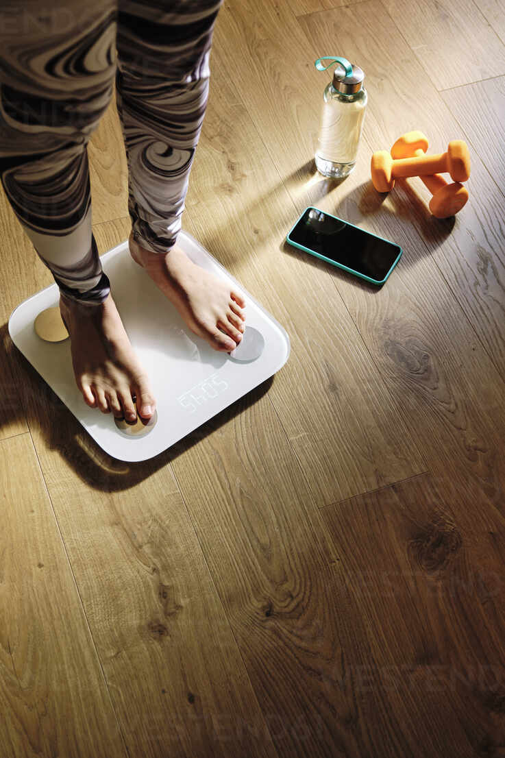 Young woman checking weight on scale at home - AODF00328 - Antonio Ovejero Diaz/Westend61
