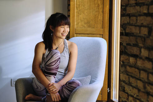 Smiling woman looking away while sitting on chair at home - AODF00331