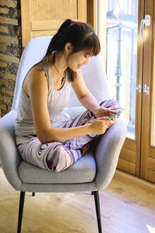 Woman using mobile phone while sitting on chair at home - AODF00334