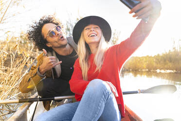 Young couple paddling in canoe, enjoying time outdoors while taking a selfie - SBOF02676