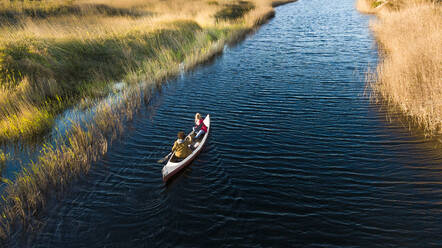 Young couple paddling in canoe in river through grasslands - SBOF02679