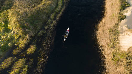 Young couple paddling in canoe in river through grasslands - SBOF02682