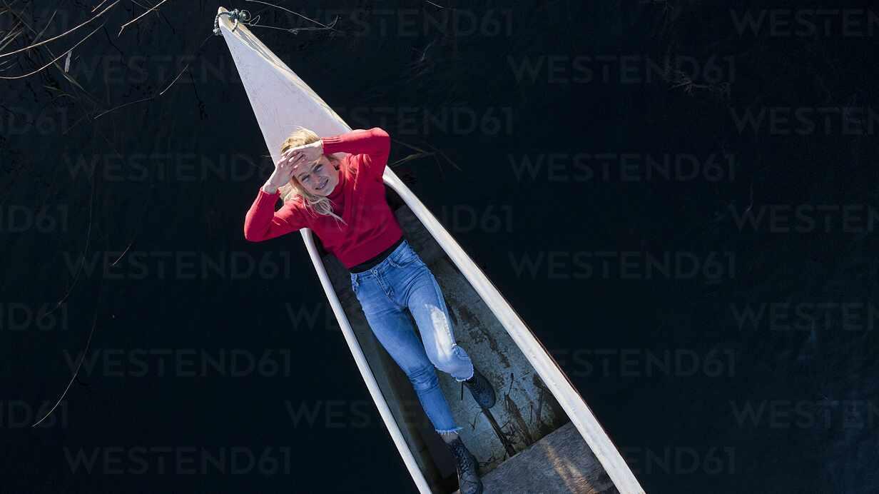 Unbekümmerte Frau lächelnd beim Ausruhen im Kanu auf dem Fluss - SBOF02685 - Steve Brookland/Westend61