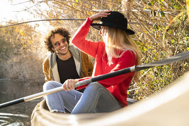 Woman adjusting hat while sitting with man in canoe on river - SBOF02688