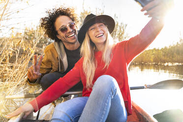 Smiling woman taking selfie with man through mobile phone while sitting in canoe on river - SBOF02691