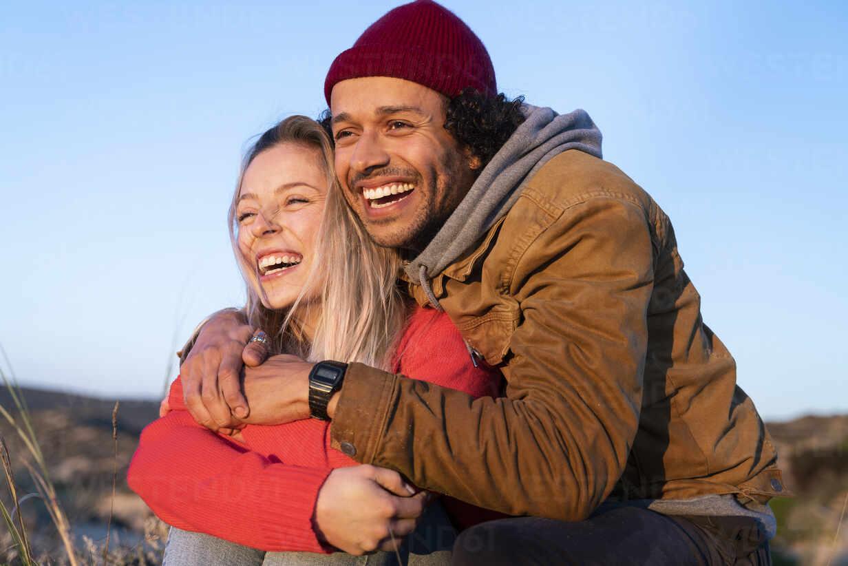 Freund umarmt Freundin von hinten, während gegen den Himmel sitzen - SBOF02694 - Steve Brookland/Westend61