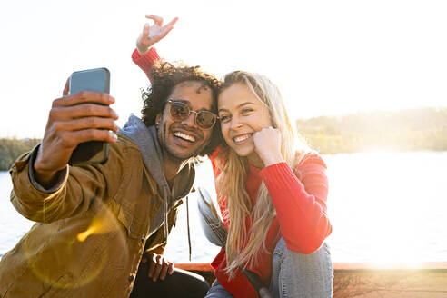 Man taking selfie with woman through mobile phone while sitting in canoe on river - SBOF02697