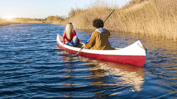 Boyfriend canoeing with girlfriend on river during sunset - SBOF02703