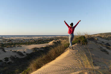 Carefree woman with hand raised walking on sand dune during sunset - SBOF02706