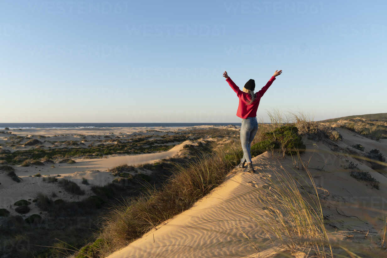 Carefree woman with hand raised walking on sand dune during sunset - SBOF02706 - Steve Brookland/Westend61