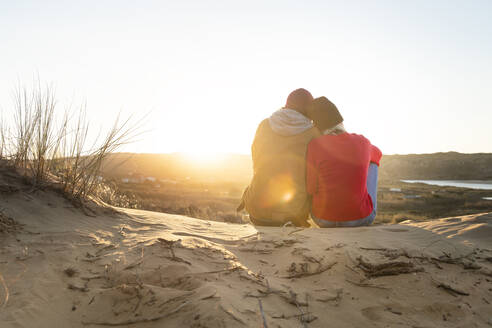 Woman leaning on man shoulder while sitting on sand dune during sunset - SBOF02709