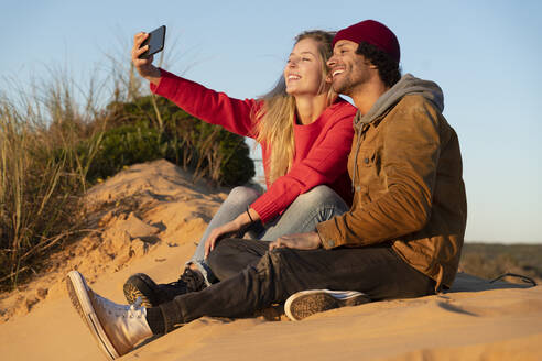 Smiling couple taking selfie through mobile phone while sitting on sand dune - SBOF02712