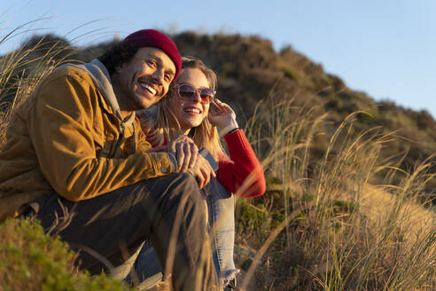 Smiling couple looking away while sitting on sand dune - SBOF02715