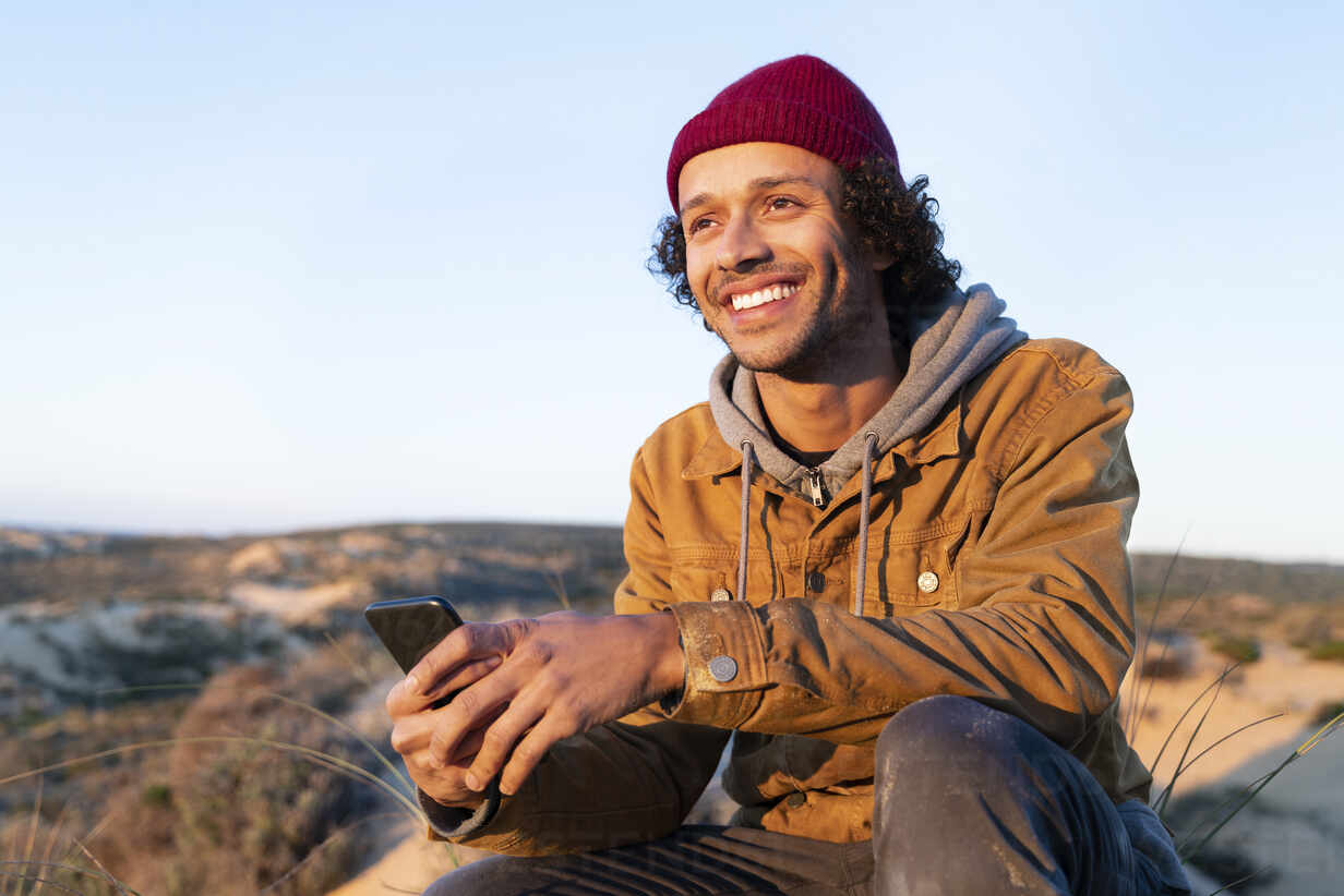 Portrait of smiling young man sitting in the dunes at sunset holding his smartphone - SBOF02721 - Steve Brookland/Westend61