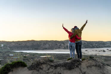 Couple standing with arm around and hand raised on sand dune during sunset - SBOF02724