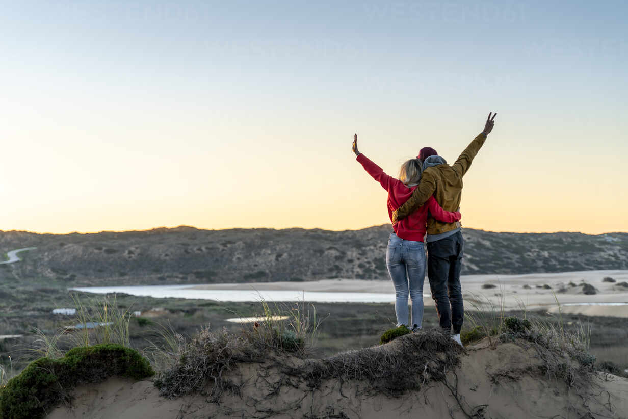 Couple standing with arm around and hand raised on sand dune during sunset - SBOF02724 - Steve Brookland/Westend61