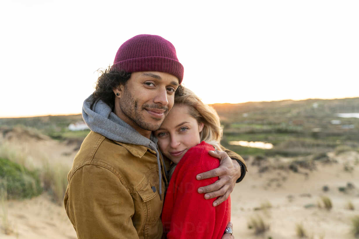Young couple in love, standing in the dunes at sunset - SBOF02730 - Steve Brookland/Westend61