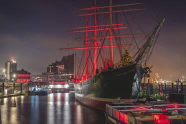 Deutschland, Hamburg, Landungsbrücken, Museumsschiff mit Weihnachtsbaum und im Hintergrund die Elbphilharmonie - KEBF01799