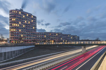 Germany, Hamburg, Amt fur Umwelt building exterior illuminated at dawn  - KEBF01823