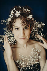 curly hair woman portrait with flowers showing sensity and feminity - GMLF00985