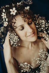 Smiling mid adult woman wearing white flowers - GMLF00988