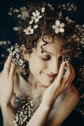 curly hair woman portrait with flowers showing sensity and feminity - GMLF00991