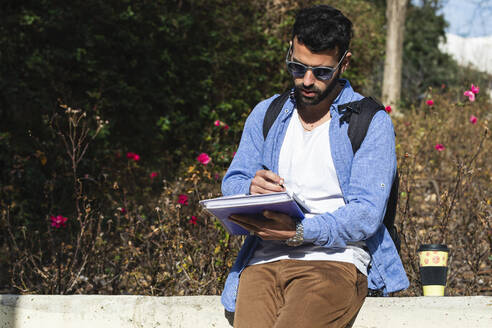 Young male entrepreneur with documents at park during sunny day - PNAF00749
