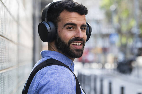 Smiling young businessman listening music through wireless headphones - PNAF00752