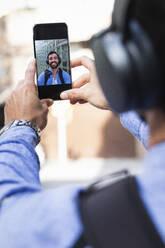 Businessman taking selfie through smart phone - PNAF00755