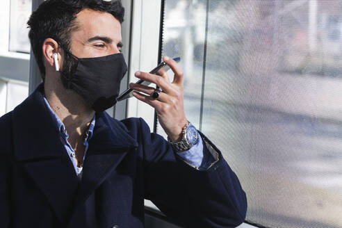 Male business professional wearing protective face mask talking on smart phone through speaker in train - PNAF00770