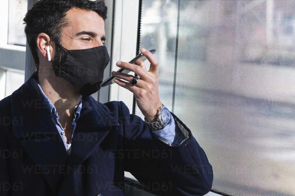 Male business professional wearing protective face mask talking on smart phone through speaker in train - PNAF00770 - NOVELLIMAGE/Westend61