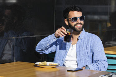 Smiling young business professional drinking black coffee while sitting at sidewalk cafe - PNAF00776