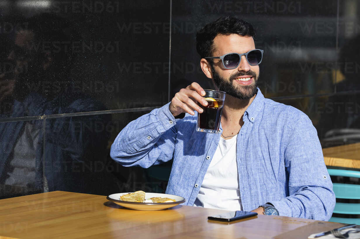 Smiling young business professional drinking black coffee while sitting at sidewalk cafe - PNAF00776 - NOVELLIMAGE/Westend61