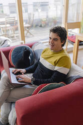 Man sitting on sofa with cat using laptop in living room - BOYF01922