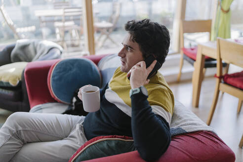Mid adult man with coffee cup sitting on sofa while talking on mobile phone at home - BOYF01928