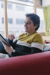 Man sitting on sofa using digital tablet in living room - BOYF01931