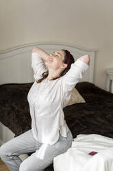Young woman relaxing on bed in bedroom. Relax, meditation, yoga, stretch, breathing techniques, breath, pranayama, raja yoga, relax, chill, leisure, sunday morning - AFVF08227