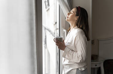 Relaxed young woman with eyes closed holding coffee cup while standing at window - AFVF08230