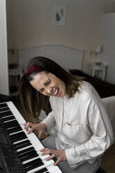 Cheerful young woman singing while playing piano in bedroom - AFVF08233