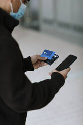 Young man using smartphone and using bank card at street with mask - OCAF00626