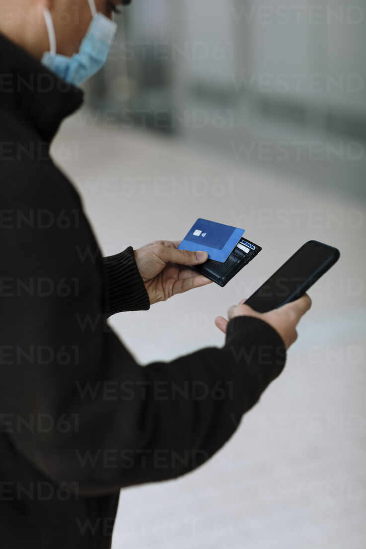Young man with credit card using smartphone while making online payment  during COVID-19 - OCAF00626 - Oriol Castelló Arroyo/Westend61