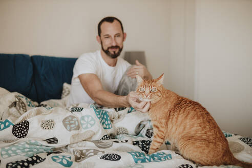 Mature man stroking ginger cat while sitting on bed - GMLF00994
