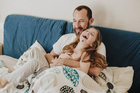 Daughter laughing with father while sitting on bed - GMLF00997
