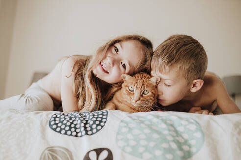 Smiling girl with brother leaning on cat in bedroom at home - GMLF01000