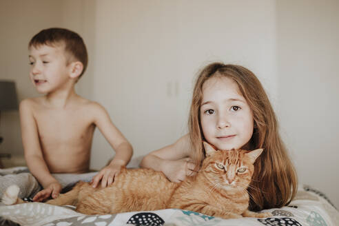 Girl leaning on cat while brother looking away in bedroom at home - GMLF01012
