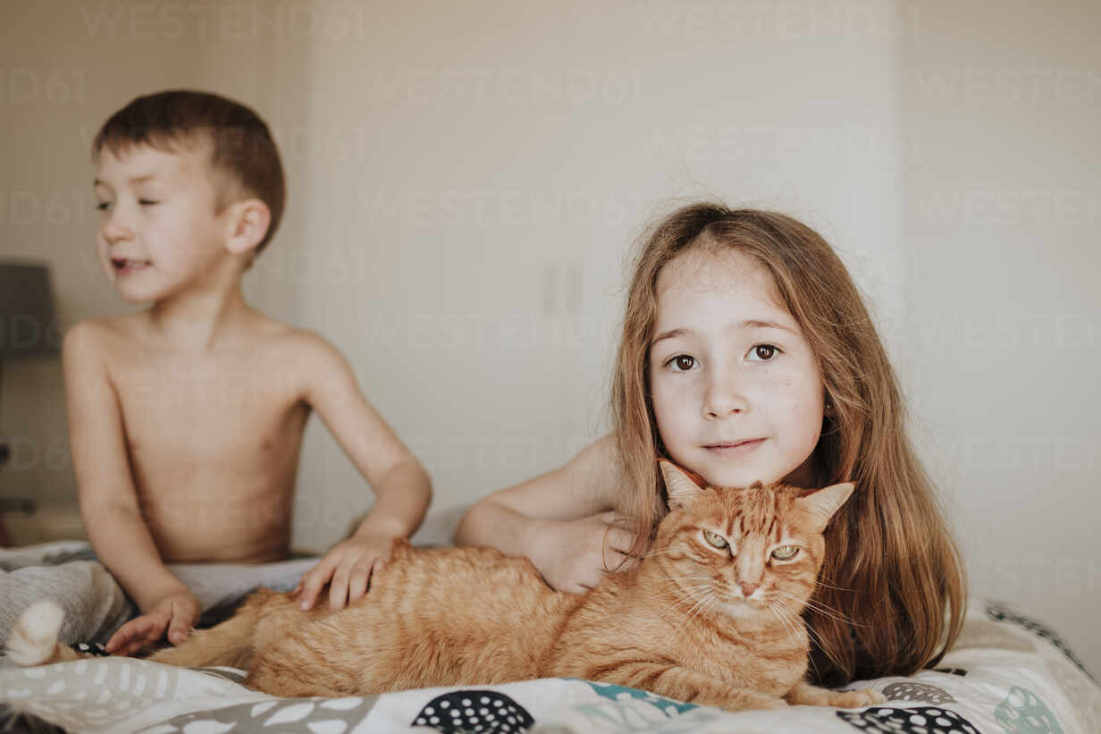 Girl leaning on cat while brother looking away in bedroom at home - GMLF01012 - Gala Martínez López/Westend61